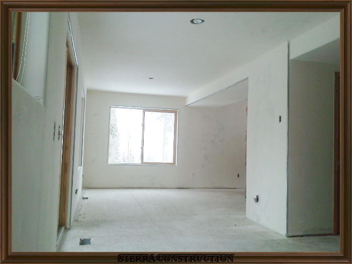 A picture in the right showing a condominium after the texture was done ready for primer and paint.