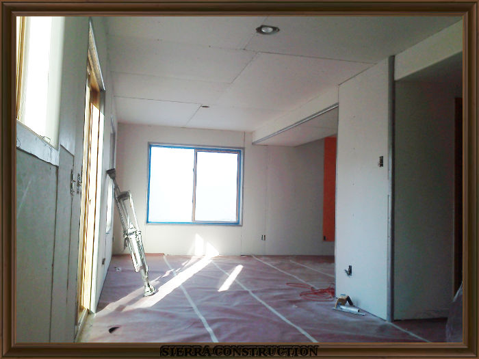 A picture in the left showing a condominium after the drywall have been installed