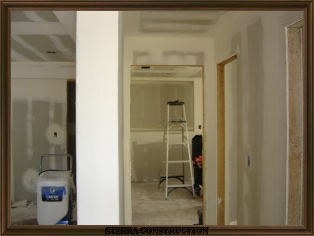 picture showing drywall finishing, taping in a big room.
