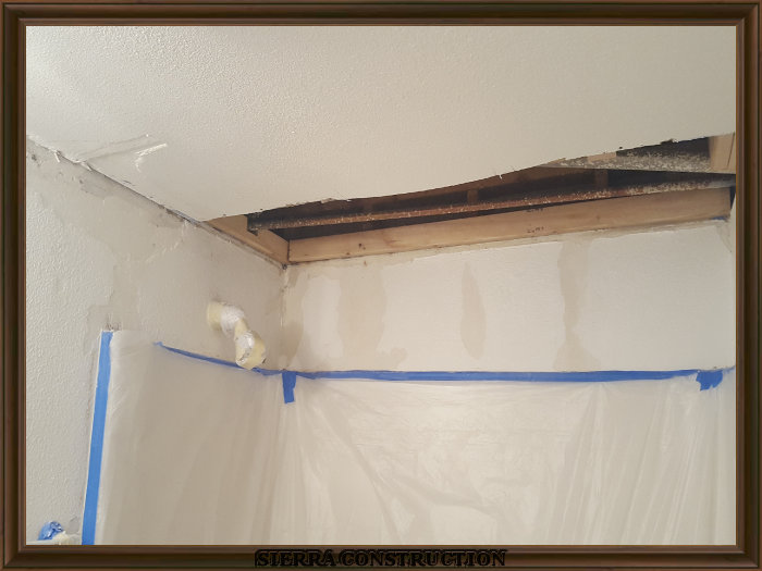 A picture in the left showing a bathroom with water damage in the ceiling and walls