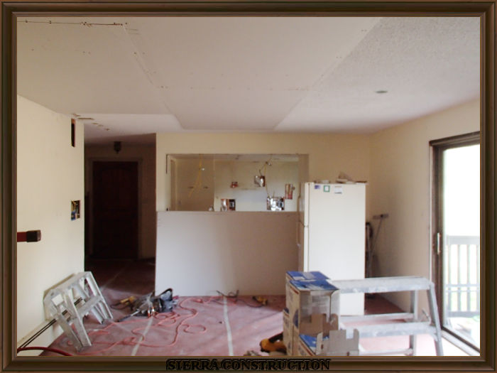 A picture in the left showing a condominium where drywall is been installed to cover the popcorn texture