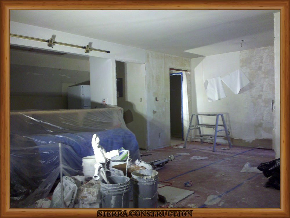 Picture showing wallpaper removal being done in a leaving room and kitchen.