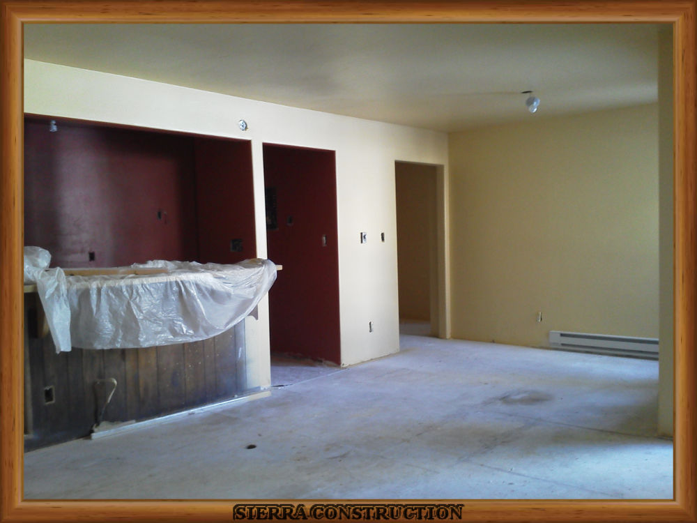 Picture showing the leaving room and kitchen after the wallpaper removal is done and it is already painted.